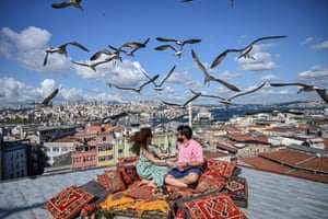 Istanbul, TurkeyA couple sit on caffe roof terrace as seagulls fly over them