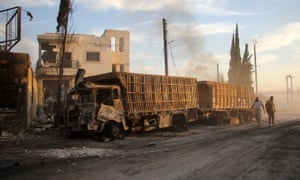 Syrians looks at the burning and damaged trucks, attacked while carrying aid into Aleppo