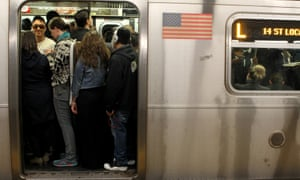 Passengers pack themselves onto a crowded L train.