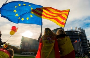 Women hold a European flag and a Catalan flag in front of the European parliament building in Strasbourg, France