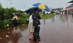 Racegoers walk in the rain during a downpour on Oaks Day at Flemington.