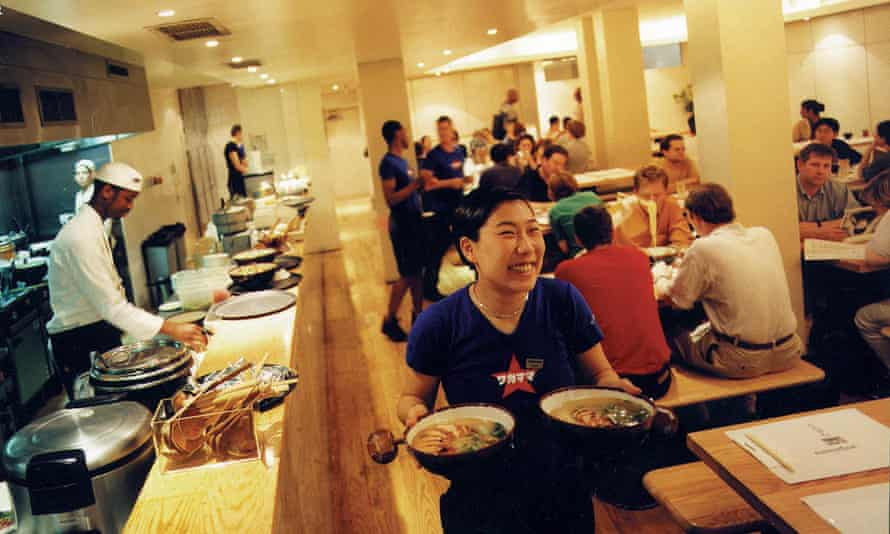 The brightly lit inside of the first ever Wagamama in London's Bloomsbury, the kitchen with chefs busy to the left and customers seated on benches and stools at tables in the background, a waitress carrying two dishes and smiling broadly in the foreground