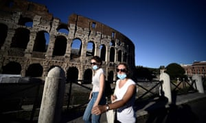 People wearing face masks walk by the Colosseum in Rome.