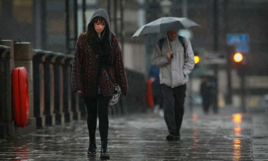 A miserable looking woman walks across Lambeth Bridge in the rain