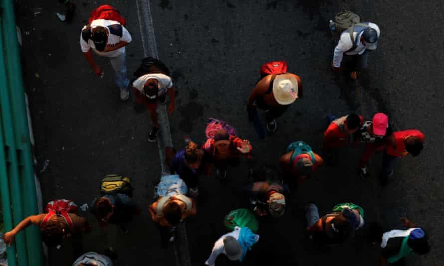 Migrants walk along the road to Huixtla, near Tapachula, Mexico, on 31 October.
