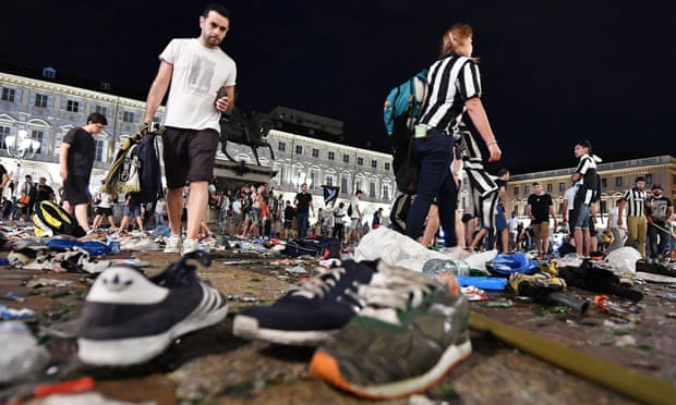 Juventus fans leave San Carlo's square at the end of the Champions League final, amid the chaos left behind by a crowd panic