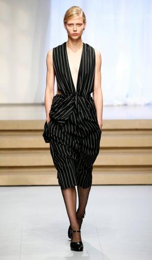 A model in the Jil Sander show wears a pinstripe V-neck all-in-one