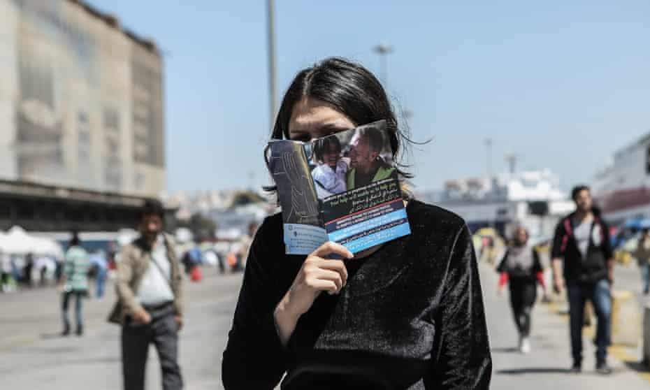 A woman hides her face behind an advice leaflet for refugees at the Piraeus passenger terminal in Athens.
