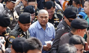 Suriyan Sucharitpolwong in October, being escorted to a court hearing