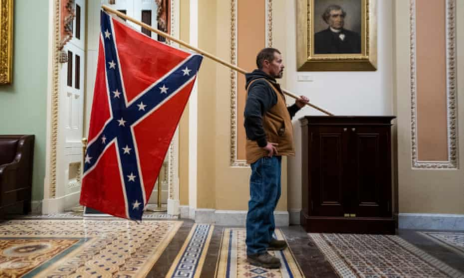 A Trump supporter carries a Confederate flag in the US Capitol on 6 January.