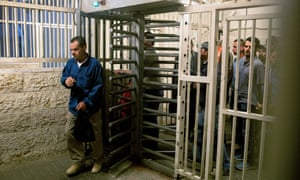 Palestinian workers queue to go through Checkpoint 300 in Bethlehem to work in Israel