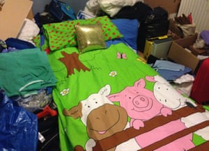 A bed in a junk room with a three little pigs duvet cover