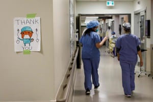 Healthcare workers walk through the hallway as staff care for patients suffering from coronavirus