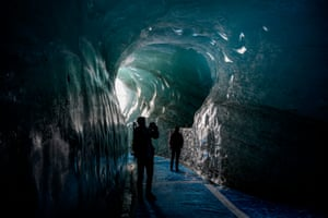People walk inside the ice cave of the Mer de Glace