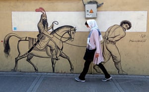 Tehran, Iran. A woman, wearing a protective mask, walks past a graffiti depicting Persian hero Rostam riding his horse behind a bound prisoner