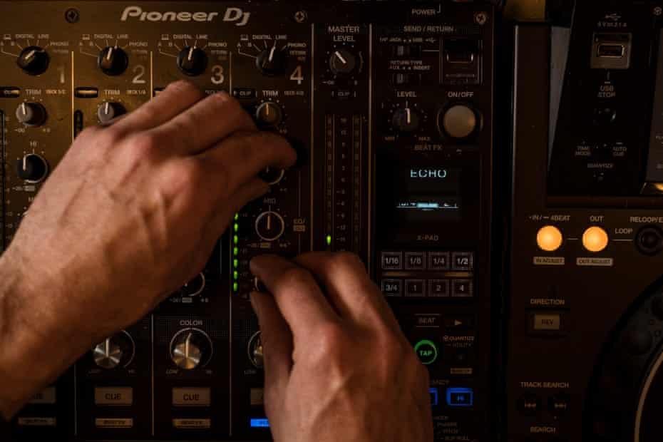 Pete Baxter adjusts volume controls on the decks of online radio station Hope St