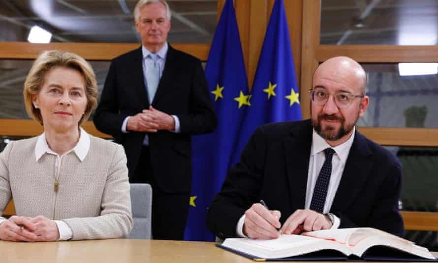 The president of the European council, Charles Michel (right), and the European commission president, Ursula von der Leyen, sign the withdrawal agreement, watched by the EU's chief Brexit negotiator, Michel Barnier, in Brussels