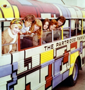 Shirley Jones, Brian Forster, Suzanne Crough, Susan Dey, Danny Bonaduce, and David Cassidy leaning out of the windows of a bus in a portrait issued for the US television series The Partridge Family, 1973