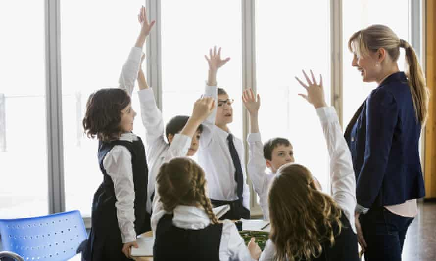 Students with hands up in class