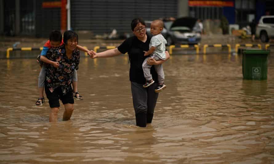 People wade through a flooded street following heavy rain in Zhengzhou, in China's Henan province