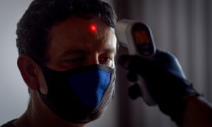 A man's temperature is checked as part of measures to slow the spread of the coronavirus