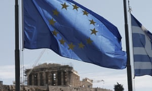 A Greek and a European Union flag billow in the wind as the ruins of the fifth century BC Parthenon temple in Athens.