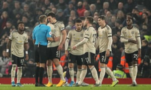 Manchester United players surround the referee.