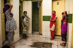 In a community toilet building in Delhi, four women wait for the one working stall to become free