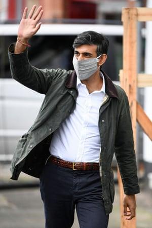 Sunak in a face mask waving as he walks along