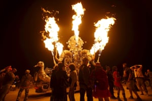 Participants gather to watch the flames from the art car El Popo Mechanico during Burning Man.