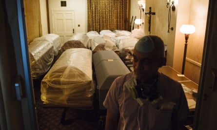 A funeral director stands in front of empty caskets for victims of Covid-19 stored in a room at a funeral home in Queens, New York, 29 April 2020.