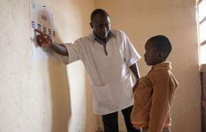 A child reads from a wall chart to test his vision