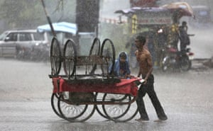 Jammu, India A man tries to protect his child from the rain by covering him with his shirt