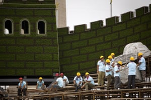 Workers take a break from building a floral replica of the Great Wall at Tiananmen Square.