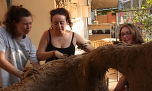 Emma Jacobs (middle) builds a mud hut.