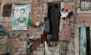 A man leaves a shelter in Sana'a with a banner on it depicting a portrait of a fighter killed in Yemene's multi-faceted conflict.