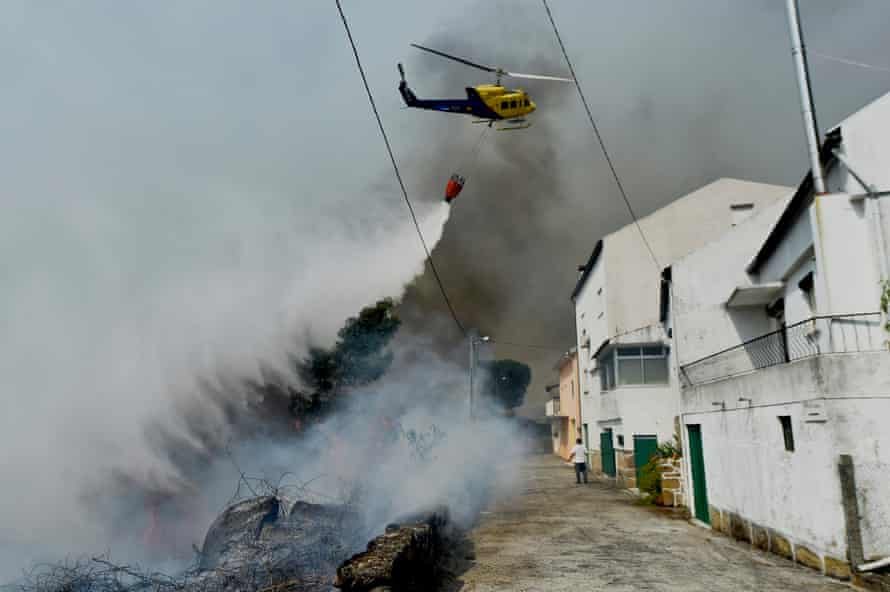 An helicopter battles the flames during a forest fire at Mangualde in Portugal on 10 August 2015. A