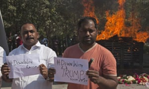 Indians hold placards in front of Srinivas Kuchibhotla's cremation pyre