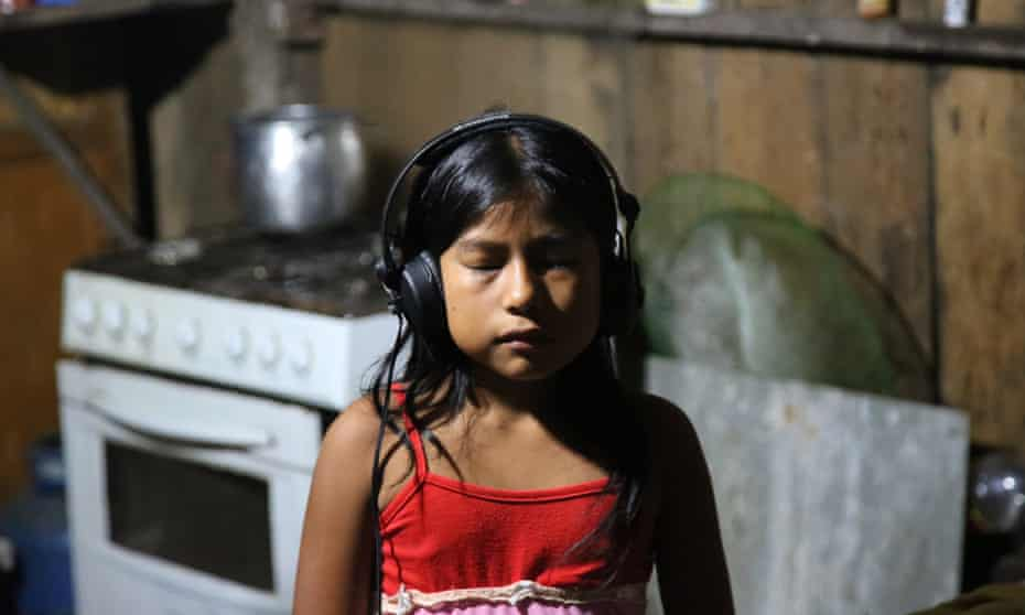 A girl from the Mayoruna community listening to Simon McBurney's binaural sound recordings.