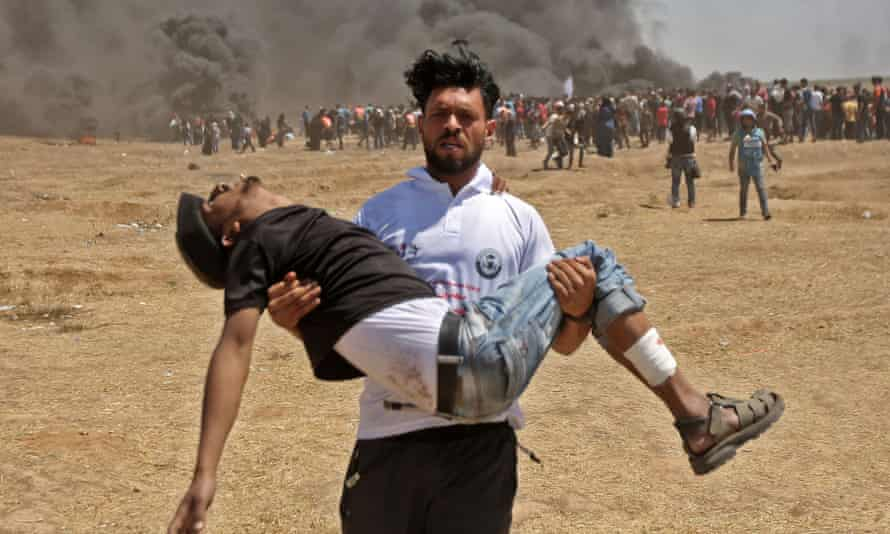 A Palestinian carries a protester injured by Israeli forces near the border between the Gaza strip and Israel