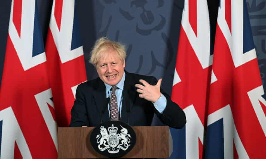 Boris Johnson speaks during a media briefing at Downing Street in London, backdropped by British union flags.