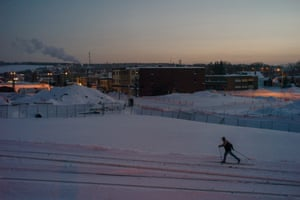 On New Year's Eve, a cross-country skier glides by the rehabilitated train tracks next to the red zone, still closed