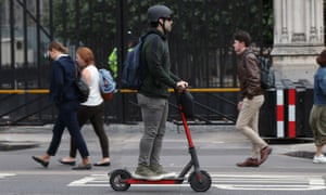 A man riding an electric scooter in Westminster, London.