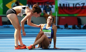 Abbey D'Agostino of the United States (R) is assisted by Nikki Hamblin of New Zealand after a collision during the Women's 5000m heat.