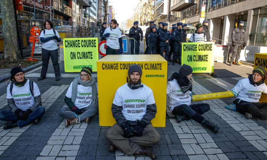Greenpeace activists block the street leading to the EU council headquarters in Brussels