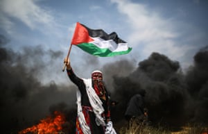 A man holds a Palestinian flag during protests at the Gaza-Israel border