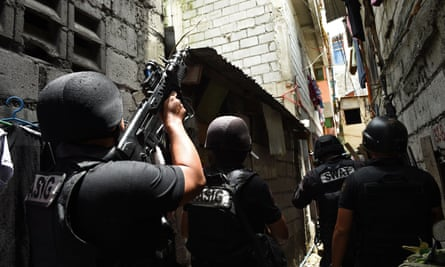 A Philippine police Swat team takes position as they serve a search warrant in relation to drugs at an informal settler house in Pasig City, suburban Manila.