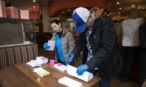 Employees of Junior's Restaurant in Brooklyn sort paychecks for fellow workers who are picking them up.
