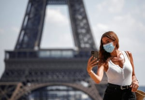 Woman takes selfie in front of Eiffel Tower