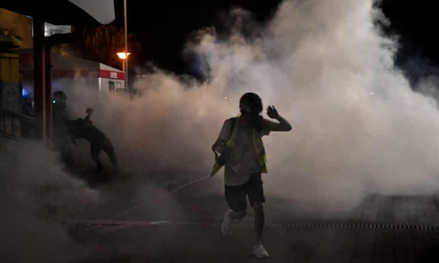 A protester runs after police fired teargas